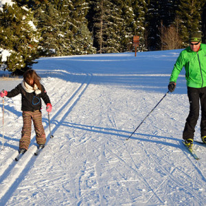 Cross Country skiing Man in green and child