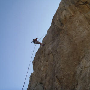 Rock Climber abseiling down cliff