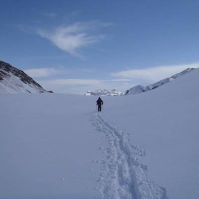 Ski touring up to the col with blue sky