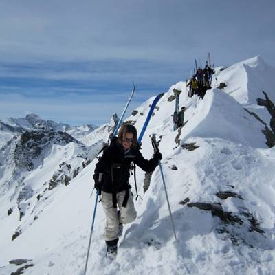 Ski touring arriving up to rocky ridge group with