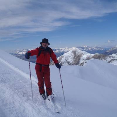 Ski touring arriving to the top man in red