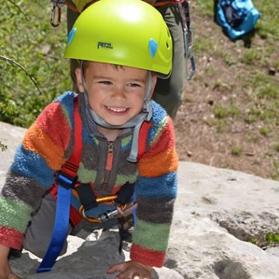 Rock Climbing little kid smiling and climbing