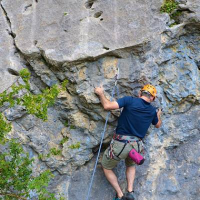 Rock Climbing man going for hold