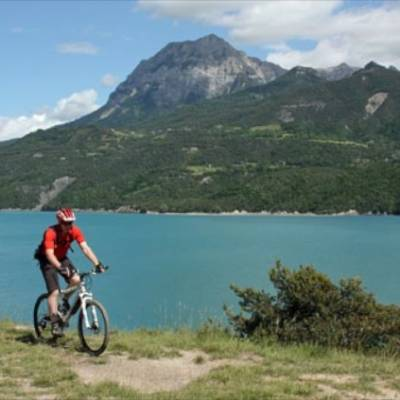 mountain biking by the sere poncon lake in Alps