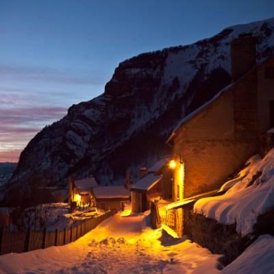 Snowshoeing view of Prapic lit up on moonlit snows