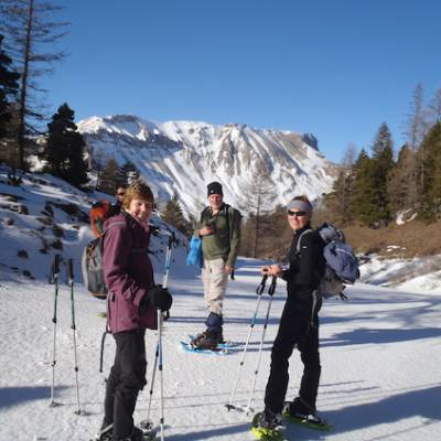 Snowshoeing group with mountain backdrop
