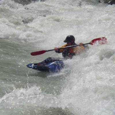 Kayaking surfing a wave in the Alps
